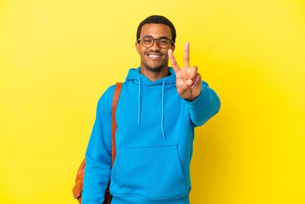 Homem estudante afro-americano sobre fundo amarelo isolado, sorrindo e mostrando sinal de vitória