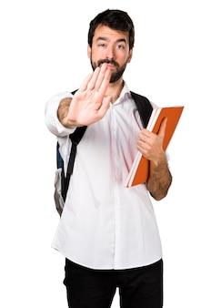 Homem estudante que faz o sinal de parada
