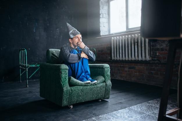 Homem estúpido em capacete de papel alumínio assistir tv, conceito de paranóia. ufo, teoria da conspiração, proteção telepática, fobia