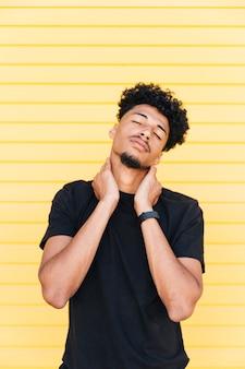 Homem étnico relaxado, esticando o pescoço com os olhos fechados