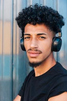 Homem étnico sério com cabelo encaracolado e fones de ouvido