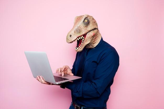 Homem eufórico com cabeça de dinossauro usando laptop