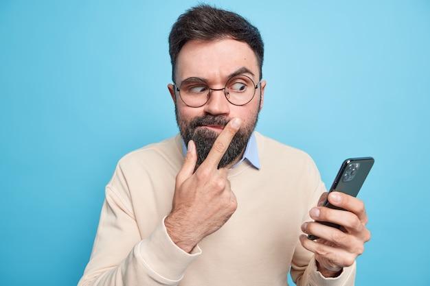 Homem europeu adulto barbudo sério e atencioso, focado no smartphone, verifica informações, lê mensagem de texto, usa gadget moderno usa óculos redondos e macacão bege