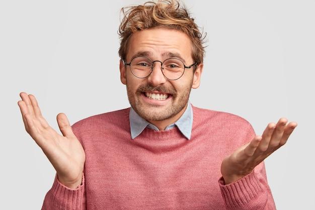 Homem europeu atraente e alegre aperta as mãos e parece sem noção, não consegue decidir o que escolher entre duas coisas