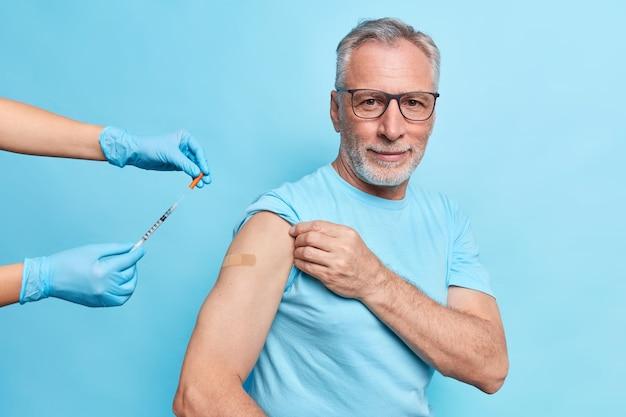Homem europeu barbudo de cabelos grisalhos recebe vacina contra coronavírus usa óculos e camiseta isolada sobre parede azul