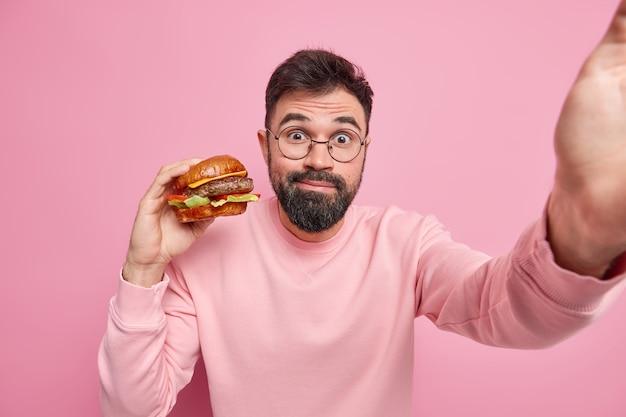 Homem europeu barbudo e bonito gosta de comer hambúrguer delicioso, tem hábitos alimentares pouco saudáveis leva selfie usa óculos redondos