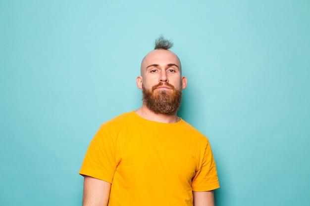 Homem europeu barbudo em camisa amarela isolado, rosto sério e brutal