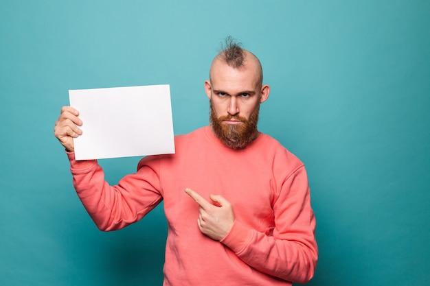 Homem europeu barbudo em pêssego casual isolado, segurando a placa de papel branco vazio rosto sério infeliz