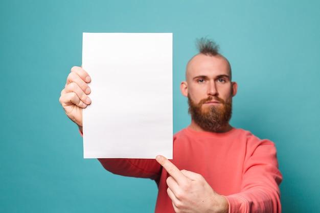Homem europeu barbudo em pêssego casual isolado, segurando o dedo indicador do tabuleiro de papel branco vazio