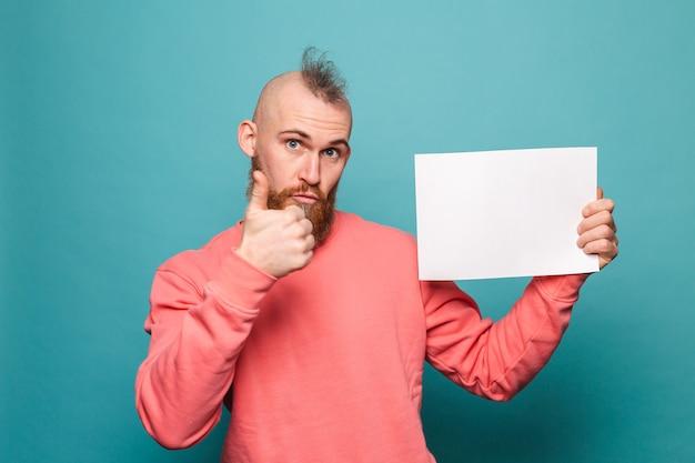 Homem europeu barbudo em pêssego casual isolado, segurando o polegar do quadro de papel branco vazio