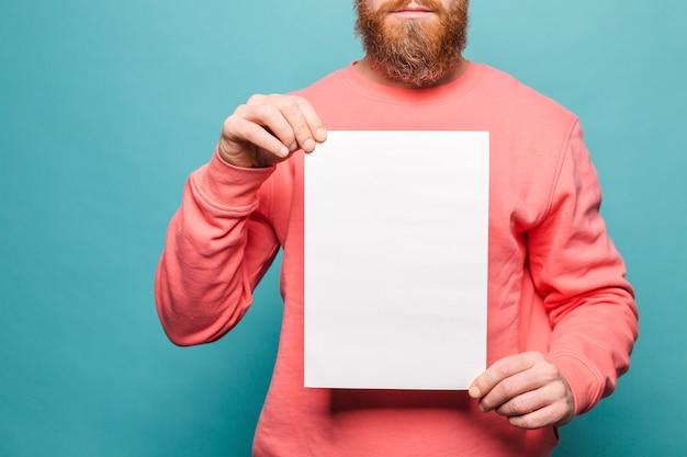 Homem europeu barbudo em pêssego casual isolado, segurando o tabuleiro de papel branco vazio