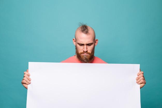 Homem europeu barbudo em pêssego casual isolado, segurando um quadro de papel branco vazio com o rosto triste e infeliz