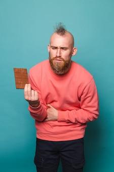 Homem europeu barbudo em pêssego casual isolado, segurar chocolate, rosto infeliz, doente, intoxicação alimentar, dor de estômago