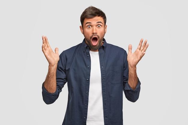 Homem europeu barbudo emotivo com expressão de espanto, gesticula com as mãos, mantém as palmas das mãos levantadas, reage a notícias repentinas, mantém o queixo caído, posa contra a parede branca. conceito de surpresa.