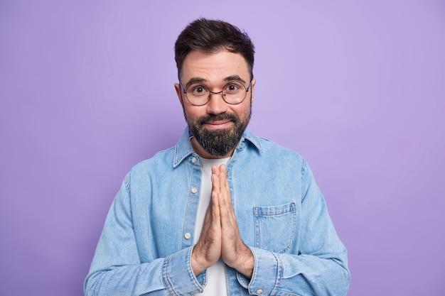 Homem europeu barbudo satisfeito mantém as palmas das mãos pressionadas e pede ajuda usa óculos redondos, camisa jeans tem expressão feliz