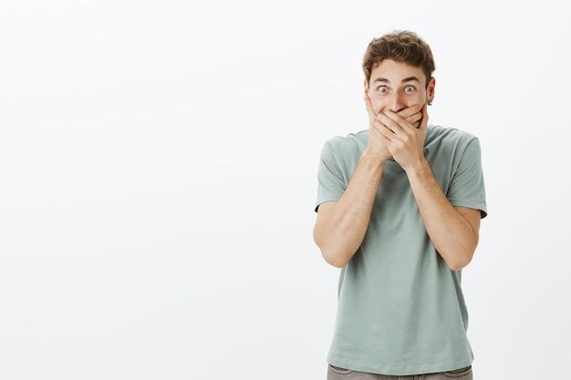 Homem europeu bonito animado com cabelo loiro em brincos, cobrindo a boca com as palmas das mãos e rindo de alegria, vendo um vídeo engraçado e rindo alto