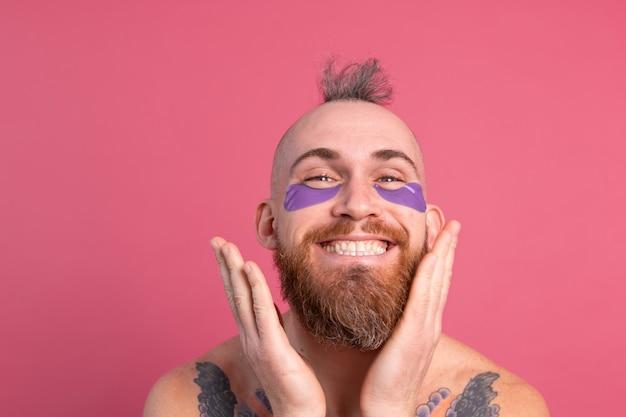 Homem europeu bonito barbudo tatuado em topless com tapa-olhos roxos, máscara posando para a câmera em rosa