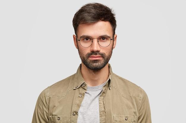 Homem europeu bonito com a barba por fazer tem uma expressão séria de autoconfiança e usa óculos