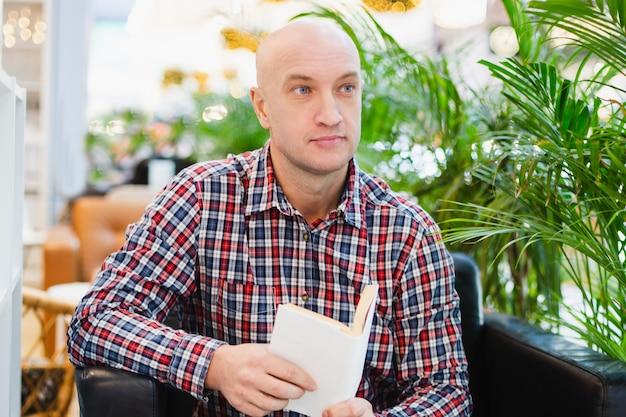 Homem europeu careca com uma camisa xadrez vermelha e jeans azul sentado em uma poltrona em um apartamento bem iluminado com muitas plantas verdes, lendo um livro em um ambiente caseiro relaxante