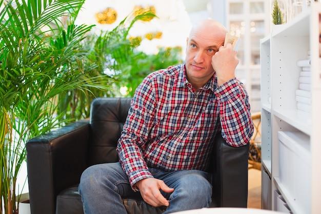 Homem europeu careca de camisa xadrez vermelha e calça jeans azul sentado em uma poltrona em um apartamento bem iluminado com plantas verdes ao fundo, pensativo com um livro nas mãos