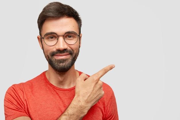 Homem europeu com a barba por fazer satisfeito com expressão alegre, barba por fazer, aponta para o lado