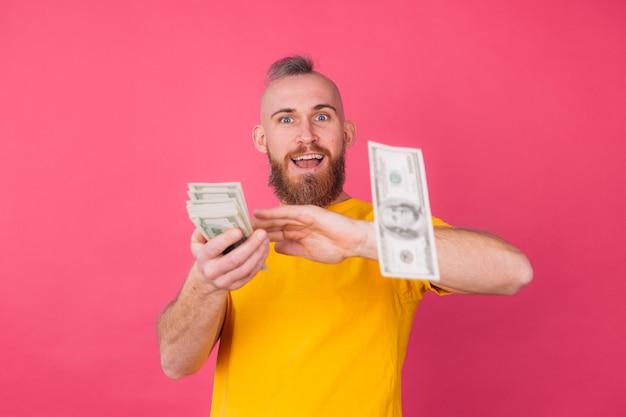 Homem europeu, com ventilador em 100 dólares feliz e animado jogando no espaço ar isolado