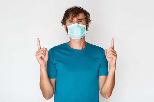 Homem europeu em máscara protetora apontando para cima