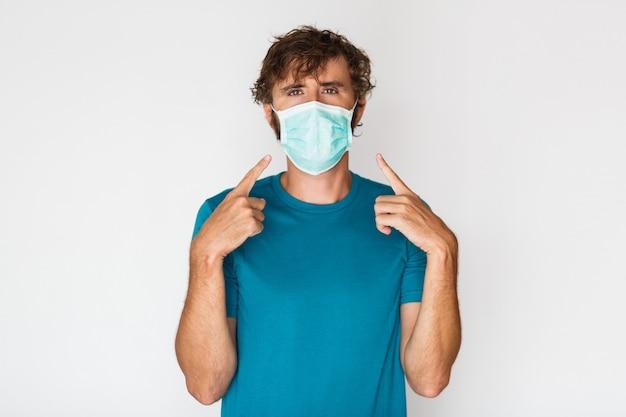 Homem europeu em máscara protetora, apontando para si mesmo