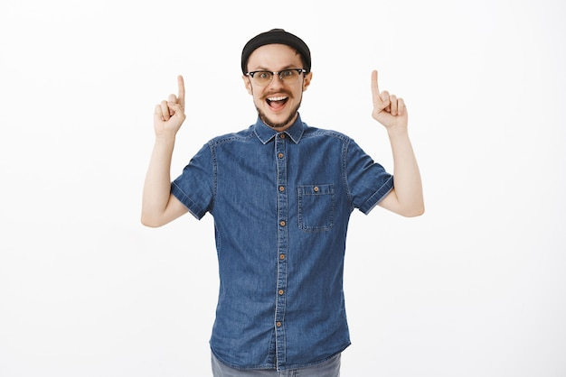 Homem europeu feliz e surpreso com barba em óculos e gorro da moda levantando as mãos apontando para cima e sorrindo amplamente de empolgação e emoção, feliz como uma criança durante uma viagem turística