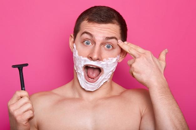 Homem europeu impressionado com olhos azuis, atira no templo, abre a boca amplamente, tem gel de barbear no rosto
