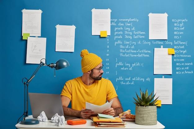 Homem europeu inexperiente olha através de documentos em papel, analisa durante o processo de trabalho