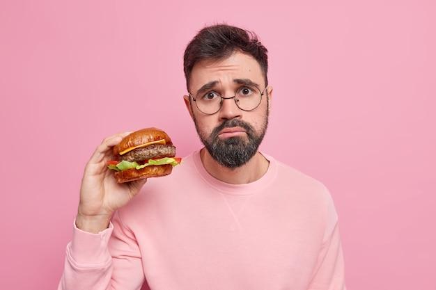Homem europeu infeliz, barbudo e faminto, recebe altas calorias lanche segura hambúrguer apetitoso come comida não saudável usa óculos redondos e suéter