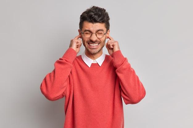 Homem europeu irritado com orelhas de plugue de barba por fazer não suporta barulho terrível