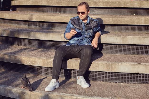 Homem europeu lê mensagens na tela do celular enquanto está sentado em degraus ao ar livre.