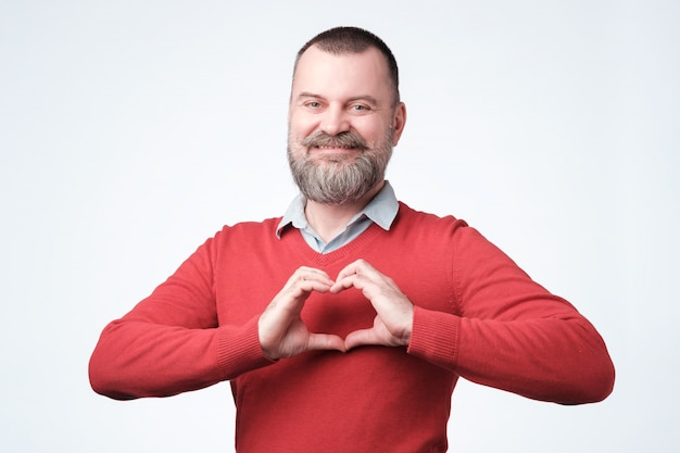Homem europeu maduro com barba fazendo o coração das mãos