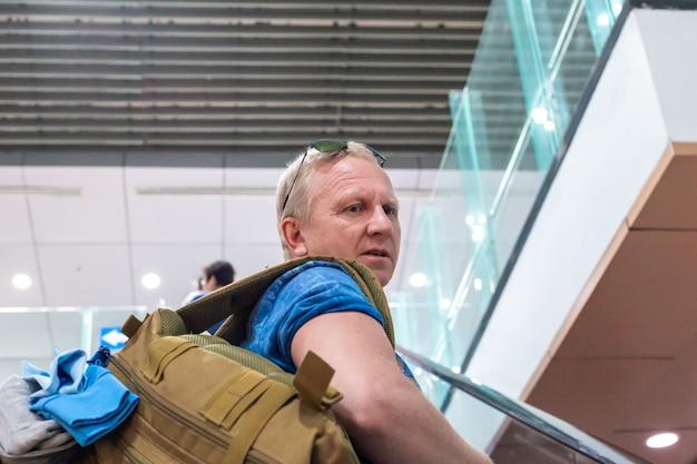 Homem europeu no aeroporto sobe as escadas olhando para trás