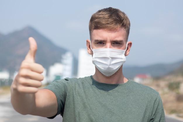 Homem europeu sério, jovem bonitão na máscara médica estéril protetora no rosto aparecer polegar, como gesto. conceito de coronavírus