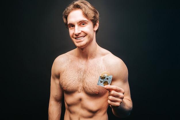 Homem europeu sorridente segurando pacote aberto com preservativo na mão. jovem cara musculoso sexual com torso desportivo nu. conceito de proteção sexual. isolado em fundo escuro. sessão de estúdio. copie o espaço