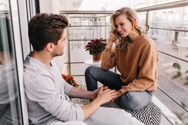 Homem europeu tocando as mãos da namorada. mulher sorridente jovial, falando com um amigo na varanda.
