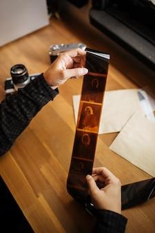 Homem examina um filme vintage de médio formato