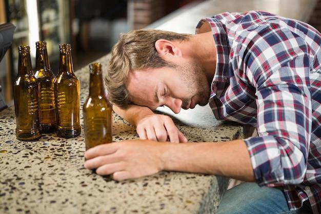 Homem exausto, inclinando a cabeça no balcão