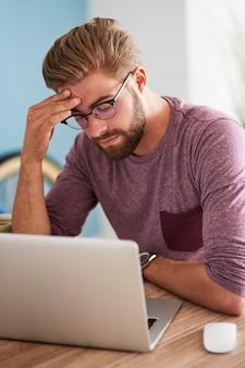 Homem exausto sobre o laptop