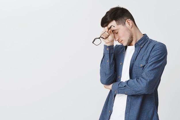 Homem exausto tirando óculos depois de muito trabalho