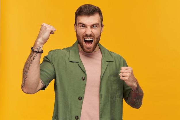 Homem excitado, cara brutal com cabelo e barba morenos. jaqueta verde de mangas curtas. tem tatuagem. levanta o punho em comemoração. isolado sobre a parede amarela