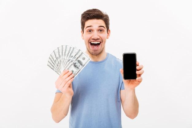 Homem excitado em t-shirt casual, segurando muito dinheiro em moedas correntes e telefone celular nas mãos, isolado sobre a parede branca