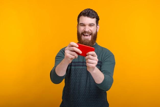 Homem excitado está jogando em seu telefone sobre fundo amarelo.