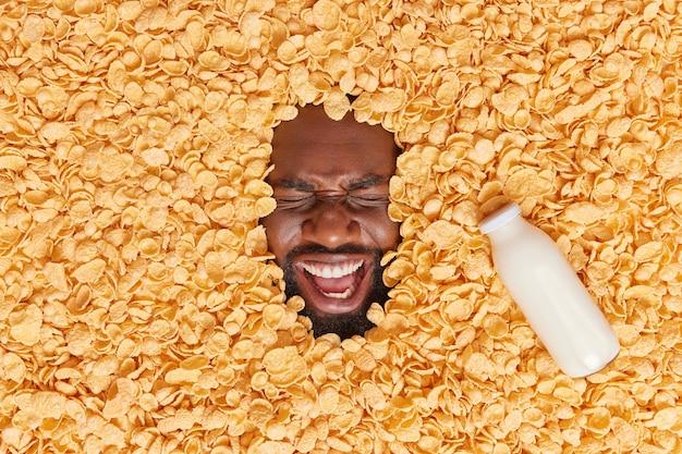 Homem exclama em voz alta com expressão de alegria rodeada de flocos de milho e garrafa de leite indo tomar café da manhã