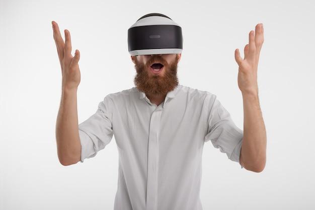 Homem exclamando e levantando as mãos, fascinado e chocado, usando um fone de ouvido de realidade virtual