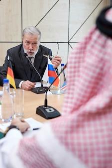 Homem executivo sênior realiza reunião política com o xeque, conversando com ele, retrovisor no homem árabe no manto tradicional vermelho. na sala de reuniões