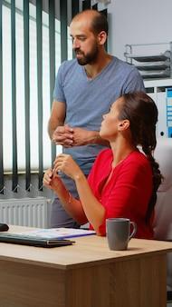 Homem explicando a solução do problema para um colega hispânico na frente do pc. equipe trabalhando em local de trabalho profissional em empresa corporativa pessoal, digitando no teclado do computador, olhando apontando para a área de trabalho